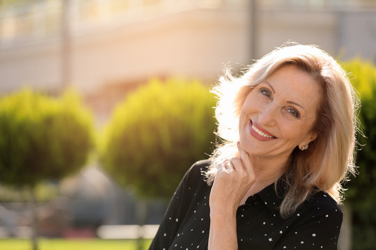 Portrait of happy mature woman in park on sunny day