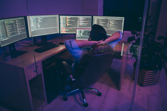 Rear back behind view of nice serious skilled genius brunet guy sitting in chair monitoring creating data database information hardware solution consultant in dark violet room workplace station