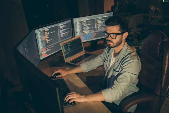 Profile side view of nice attractive serious smart clever bearded brunet guy sitting in chair editing creating database bug tracking report web content display in dark beige room workplace station