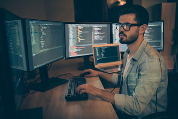Photo of serious administrator responsible for cyber security of large corporation searching for safety gaps debugging existant operating system to reduce hacker attacks success probability Wall mural