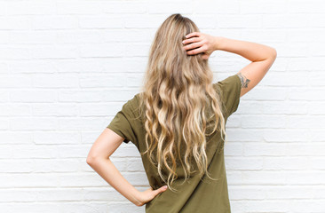 young blonde woman thinking or doubting, scratching head, feeling puzzled and confused, back or rear view against brick wall background