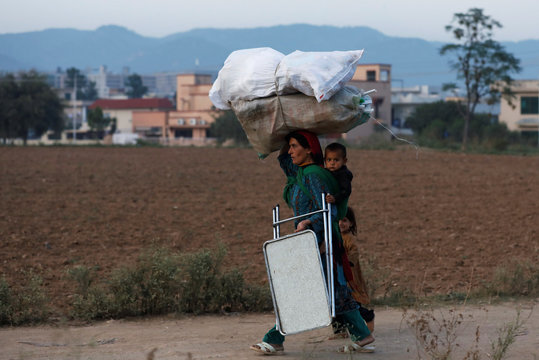 A woman carries sacks of wood, to be used as fuel for cooking and heat during the winter season, while heading home with children in low income neighborhood in Islamabad,