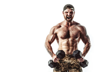 Muscular athlete bodybuilder man in camouflage pants with a naked torso workout with dumbbell on a white background. Isolate