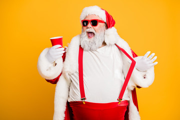 Funky big belly christmas grandfather in red x-mas hat headwear visit noel party hold disposable glass cup mug with beer feel crazy isolated over yellow color background