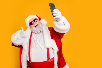 Funky overweight white beard hair santa claus grandfather red costume blogger make selfie on smartphone have summer travel show thumb-up sign wear hat cap suspenders isolated yellow color background