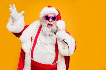 Portrait of fat big belly crazy funky santa claus hold microphones have live x-mas performance sing carols on christmas night wear red hat headwear trendy suspenders isolated yellow color background