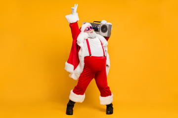 Full size photo of funny overweight christmas white beard hair grandfather hold retro boombox show v-signs have fun on x-mas celebration wear stylish hat suspenders isolated yellow color background
