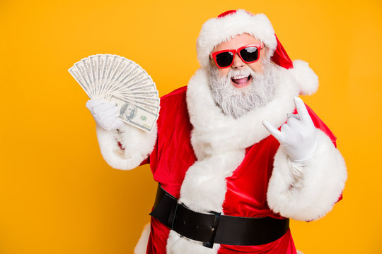 X-mas lottery win credit bank present for noel. Funky crazy hipster white bearded santa claus hold money fan show horned symbol enjoy deposit gift wear red hat isolated yellow color background