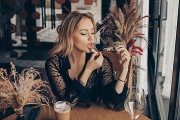 Fashionable beautiful girl applies lip make-up with peach lipstick while sitting at a table in an elegant interior. fashion portrait stylish curly blonde girl in a black jacket. Caucasian young woman Wall mural