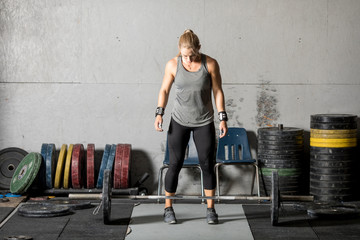 Strong young female weight lifter preparing for heavy lift in gym.