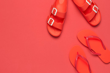 Wall Mural - Fashionable beach coral flip flops and sandals on bright coral background. Flat lay, top view, copy space. Creative beach concept, stylish summer shoes, vacation, travel. Trend coral color