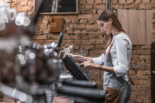Young woman at counter with cashbox working in coffee shop