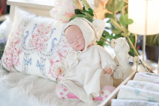 Baby doll. Soft focus and dreamy effect of a cute sleeping baby doll next to rabbit statue.