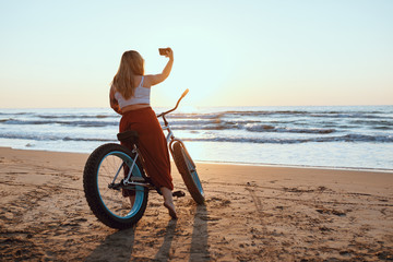 Cheerful chubby woman taking selfie on smartphone while resting with bicycle at sunny shore