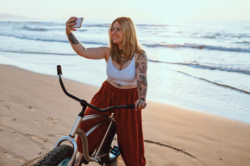 Smiling content tattooed woman in glasses taking picture on smartphone while standing with bike at peaceful beach