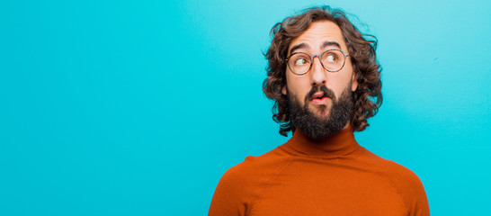 young bearded crazy man with a worried, confused, clueless expression, looking up to copy space, doubting against flat color wall