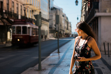 Confident beautiful woman in summer dress holding a photo camera while standing on scenic sunny city street in Lisbon, Portugal