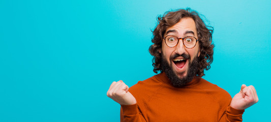 young bearded crazy man feeling shocked, excited and happy, laughing and celebrating success, saying wow! against flat color wall Wall mural