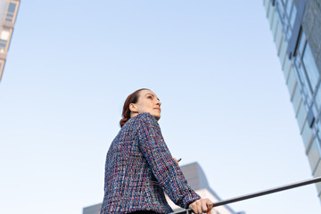 Low angle of serious female manager in elegant outfit leaning on railing and looking away while standing outside modern office building