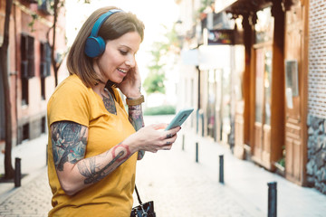 Attentive hipster tattooed woman in headphones using smartphone while standing on sunny city street