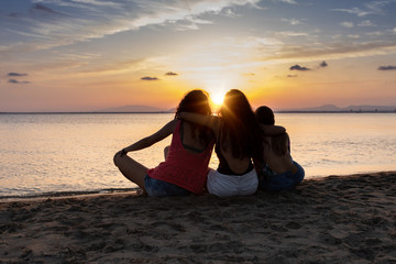 Back view of bronzed female friends hugging and relaxing on beach at sunset in summer in back lit Fototapete
