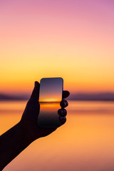 Silhouette of a man taking a sunset picture with his mobile