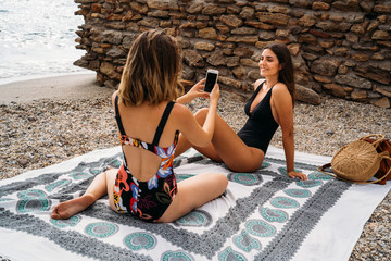 Stylish young women in swimwear relaxing on seashore taking picture by smartphone and looking at each other