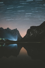 Blue rays of light shining at beautiful tranquil night with clear starry sky on lake in Dolomites mountains during fair weather