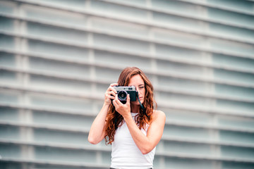 Stylish woman with red hair adjusting photo camera in hand and looking through viewfinder