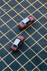 From above view of red taxi cars crossing box junction with yellow cross lines