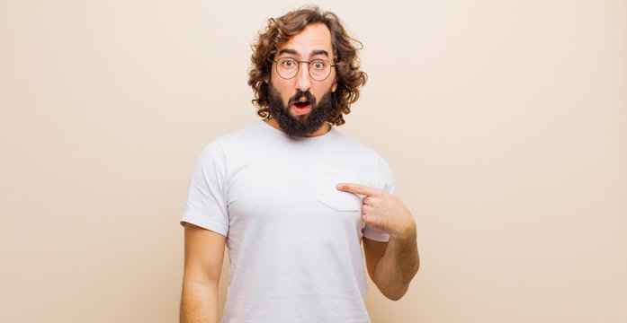 young bearded crazy man feeling confused, puzzled and insecure, pointing to self wondering and asking who, me? against flat color wall
