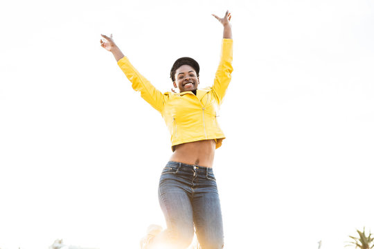 Low angle of happy African American woman in stylish bright jacket jumping with hands up on white background
