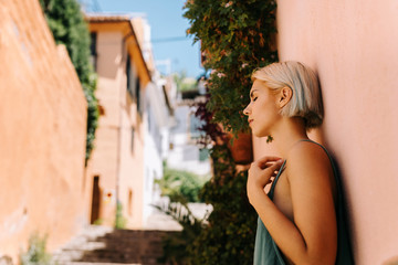 Side view of beautiful young female with short blond hair closing eyes and leaning on wall while standing on blurred background of town street on sunny day