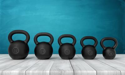 3d rendering of five black kettlebells on white wooden floor and dark turquoise background