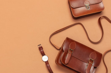 Brown leather women bag, stylish wristwatch on brown beige background top view flat lay copy space. Fashionable women's accessories. Sales Fashion Concept. Stylish Lady Clothes. Luxury Leather Bag
