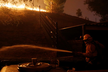 A firefighter hoses a hot spot while battling the Kincade fire in Geyserville, California