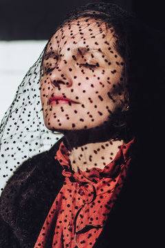 Portrait of a woman with a black dotted veil