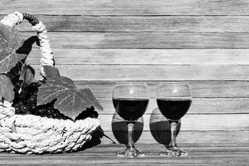 two glasses of red wine and a basket of grapes on a wooden background on a Sunny day with a copy of the space, black and white photo