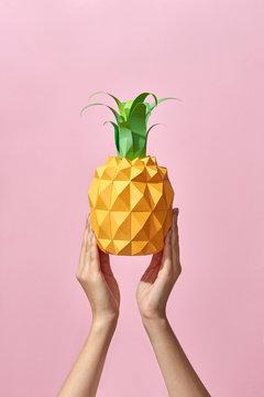 Pineapple with green leaves made of paper holds the hand of a girl on a coral background with space for text. Handcraft Tropical Fruit. Pantone 16-1546 Living Coral is the color of the year 2019.