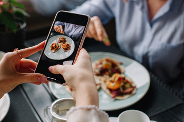 Unrecognizable woman taking photo of her friend's plate