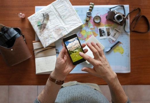 Man using a phone and planning a trip