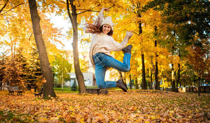 Happy young woman jumping with raised arms on colorful autumn leaves city background