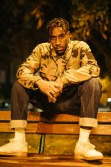 Black man sitting on bench at night