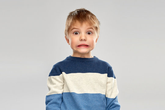 childhood, expressions and people concept - shocked little boy in striped pullover over grey background