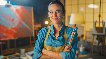 Fototapete - Talented Young Female Artist Dirty with Paint, Wearing Apron, Crosses Arms while Holding Brushes, Looks at the Camera with a Smile. Authentic Creative Studio with Large Canvas and Tools Everywhere