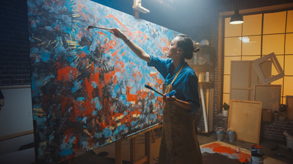 Fototapete - Talented Female Artist Works on Abstract Oil Painting, Using Paint Brush She Creates Modern Masterpiece. Dark and Messy Creative Studio where Large Canvas Stands on Easel Illuminated