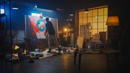 Fototapete - Talented Male Artist Working on an Abstract Painting, Uses Industrial Roller To Paint Daringly Emotional Modern Picture. Dark Creative Studio Large Canvas Stands on Easel Illuminated.