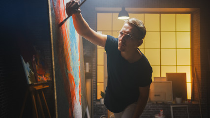Fototapete - Talented Artist Working on Abstract Painting, Uses Paint Brush To Create Daringly Emotional Modern Picture. Dark Creative Studio Large Canvas Stands on Easel Illuminated.