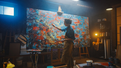 Fototapete - Talented Female Artist Working on a Modern Abstract Oil Painting, Gesturing with Broad Strokes Using Paint Brush. Dark Creative Studio Large Picture Stands on Easel Illuminated, Tools Everywhere