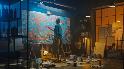 Fototapete - Talented Female Artist Works on Abstract Oil Painting, Using Paint Brush She Creates Modern Masterpiece. Dark and Messy Creative Studio where Large Canvas Stands on Easel Illuminated.